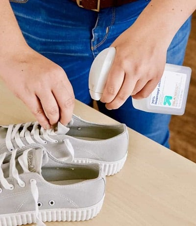 man die een spray van alcohol toepast op canvas stinkende schoenen