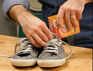 voorbeeld van man die baking soda in stinkende schoenen strooit