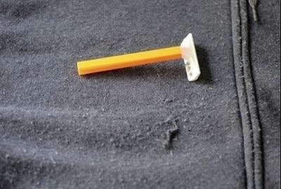 wegwerp scheermes op een zwart kledingstuk voor het verwijderen van pluizen