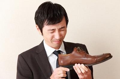 man met vies gezicht boven stinkende schoenen van leer
