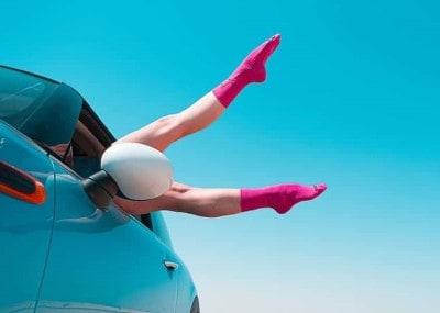twee vrolijke benen uit een autoraam met roze sokken