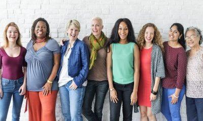 8 vrouwen lachend op een rijd met verschillende stijlen kleding aan