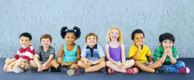 7 kinderen op een rij in verschillende kleuren kleding