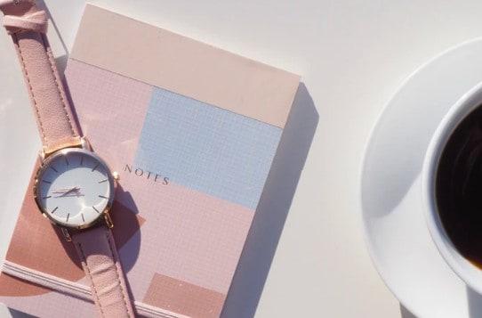 roze horloge op notietieboek met kopje koffie er naast
