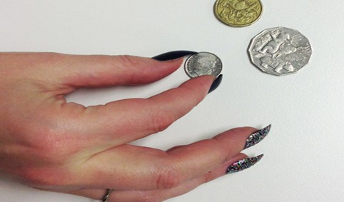 vrouwenhand met acrylnagels die een muntje probeert te pakken