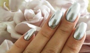 zilver gelakte nagels boven een bed van bloemen