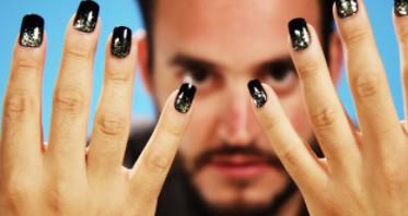 man uit focus in achtergrond met zichtbare nagels in het zwart op de voorgrond